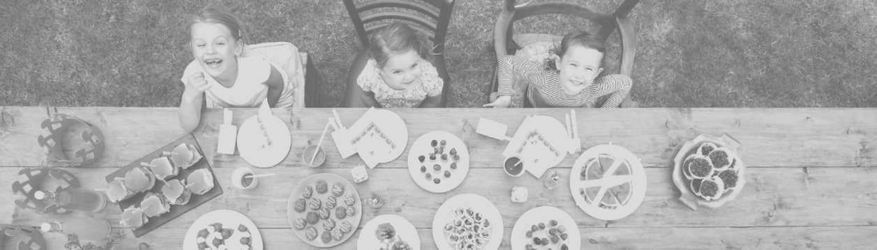 Three girls sitting at table with different finger foods.